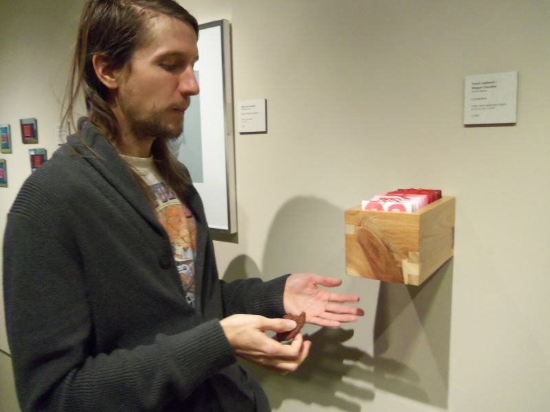 """Travis says, """"Look ma, no hands,"""" through a mouthful of chocolate cookie.  For what it's worth, the gallery may not know how to display work, but it sure knows where to get the good cookies."""